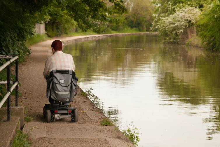 A disabled person drives a disability scooter down a canal towpath