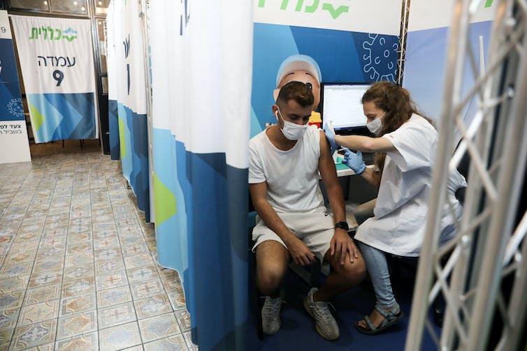 An Israeli man receiving his third vaccine dose