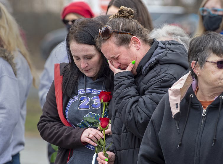 Two women weep and carry red roses.