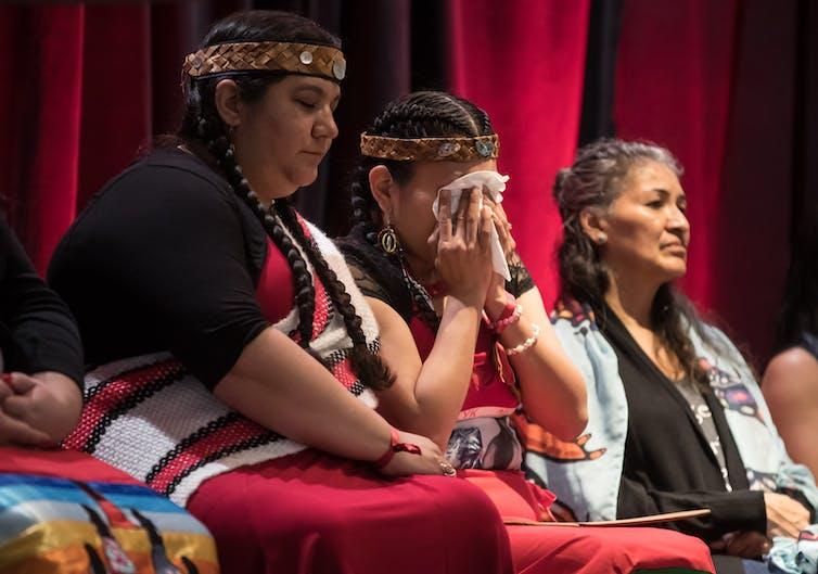 An Indigenous woman wipes away tears.