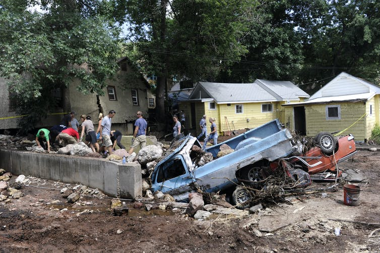 People search through damaged homes and vehicles, including an old truck nose down in the foundation of a home that's no longer there.