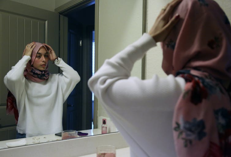 Teenager adjusts her hijab in mirror