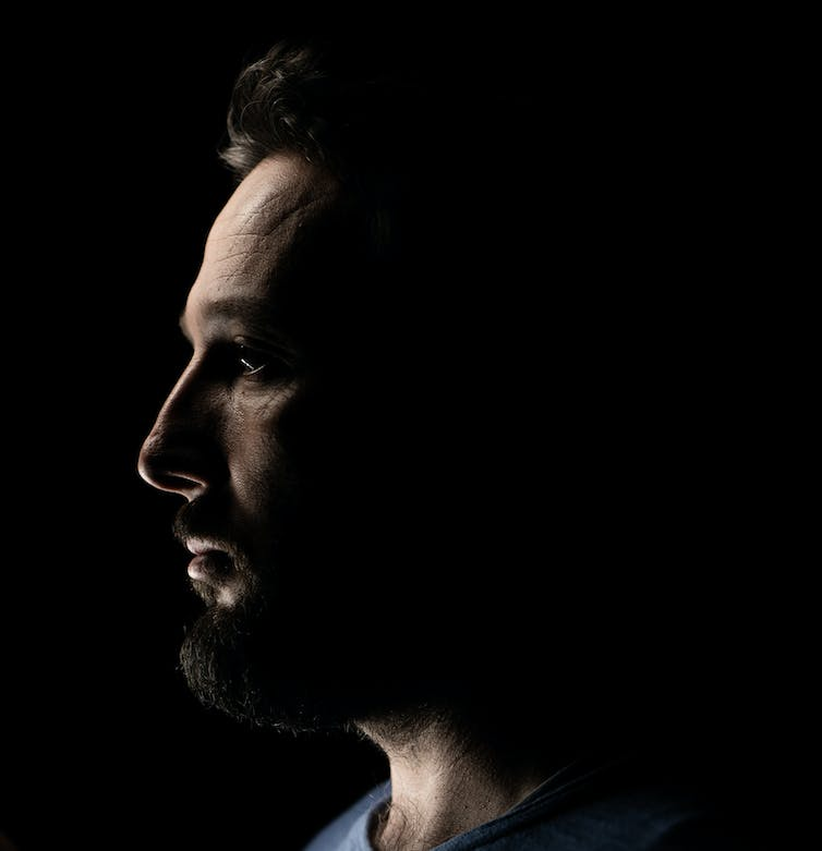 Close-up profile of person with beard on a dark background.