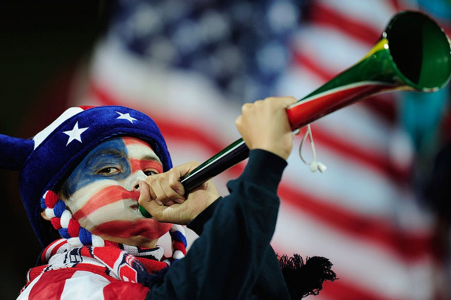 Boy with red, white and blue face paint and wearing a hat with stars on it blows a trumpet-like instrument; US flag in background