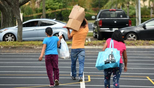 A families carrying boxes and bags walk away from a food distribution center in Florida.