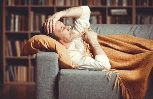A man with a breakthrough infection lying on a couch
