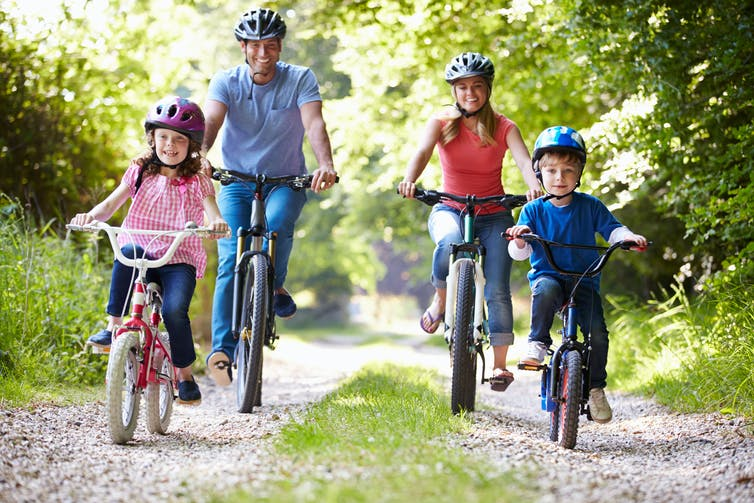 A family cycling in a park.