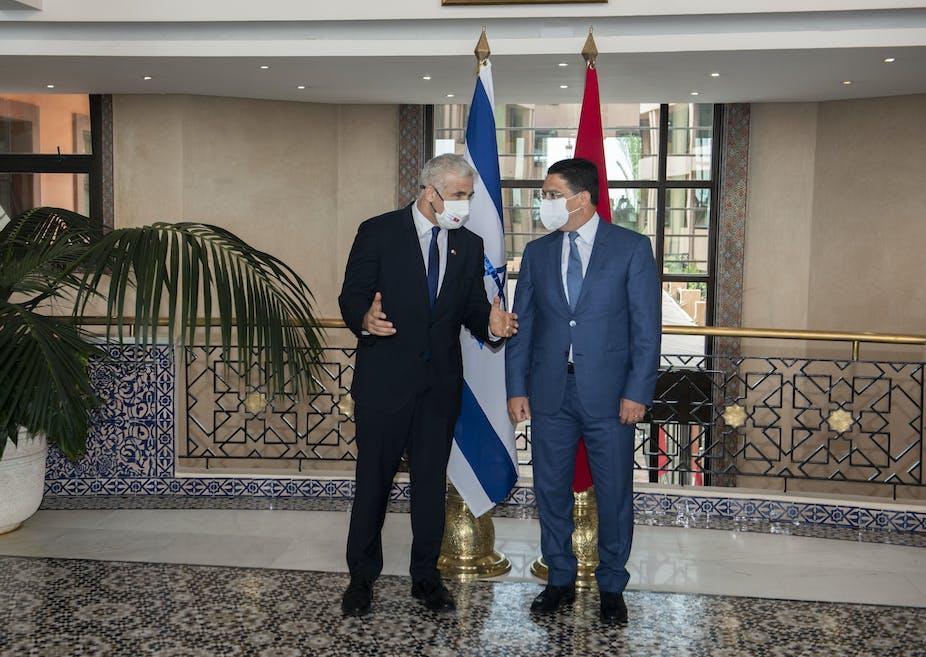 Dos hombres vestidos con trajes y máscaras COVID-19 charlan de espaldas a la bandera de Israel a la izquierda y la de Marruecos a la derecha.