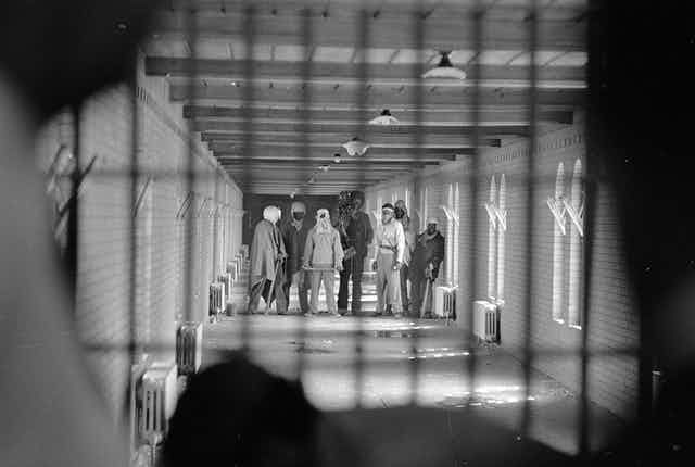 Prisoners wearing cloaks and football helmets stand behind bars as they begin negotiations with New York State officials in 1971's Attica standoff.