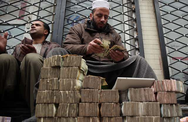 An Afghan money changer counts a pile of currency in Kabul as many piles of Aghani notes sit int he foreground