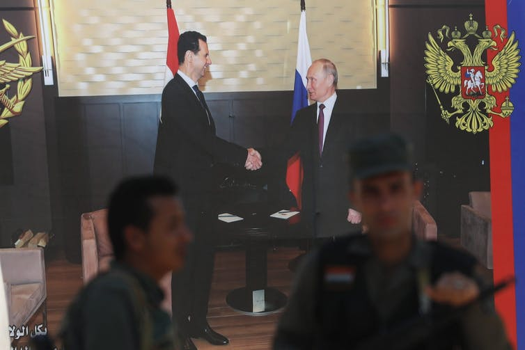 Syrian policemen stand guard in front of poster of Syrian President Bashar Assad and Russian President Vladimir Putin