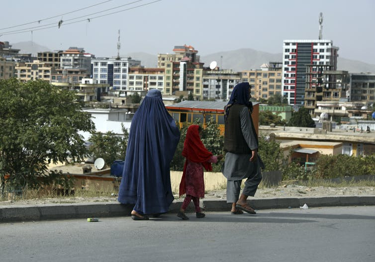Afghan people walk on a street in Kabul with high-rises in the background.