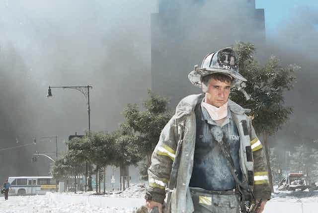 A New York City firefighter walks away from Ground Zero on 9/11