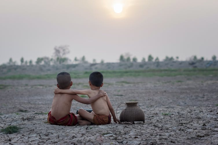 two boys with arms around each other on cracked earth