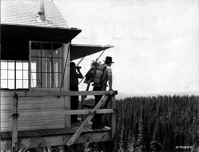 In an old photo, two people stand on a tall fire tower overlooking miles of pines trees.