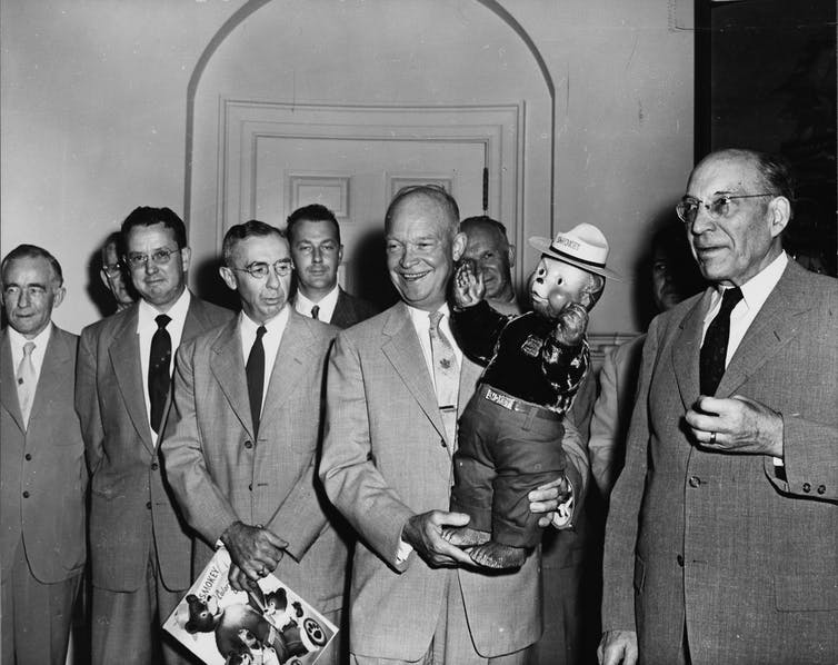 President Eisenhower Smiles As He Holds Up The Toddler-Sized Smokey Bear Doll With Men In Suits Flanking Him.