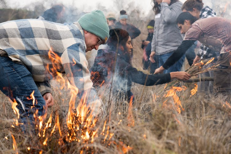 People Wearing Jackets Against The Cool Weather Light Small, Controlled Fires In Grasslands