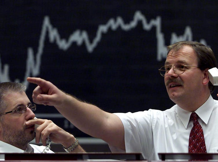 Financial trader on the phone with a market chart behind him