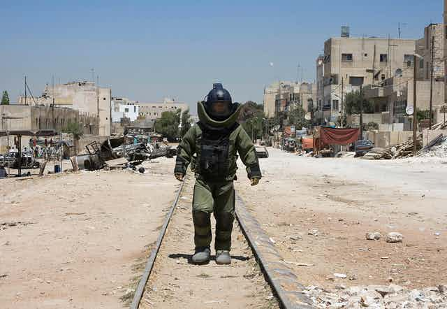 Man in bomb disposal suit walking down train track.