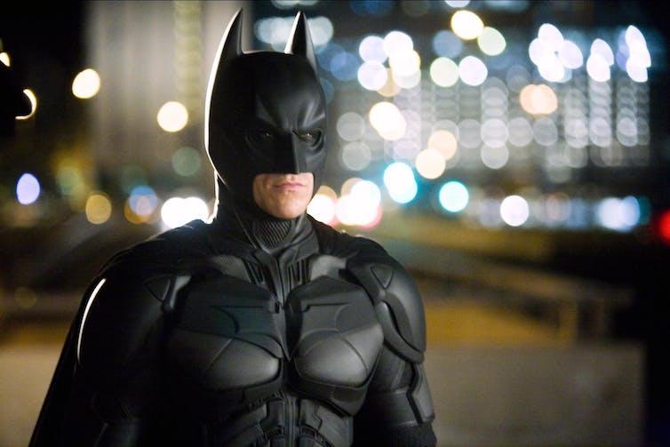 Batman stands in front of buildings.