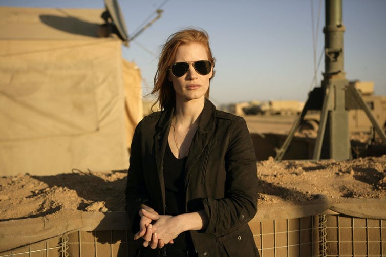 Woman dressed in black against military base backdrop.