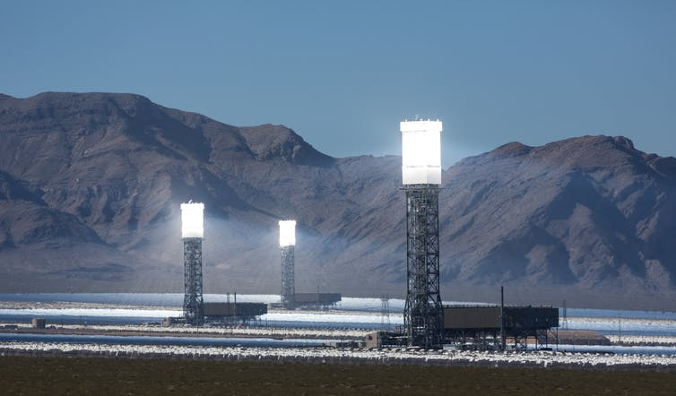 Three glowing solar towers in the desert.