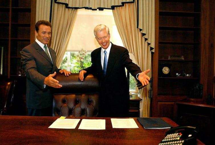 Gov.-election Arnold Schwarzenegger and Governor Gray Davis standing behind Davis' desk at the state Capitol.