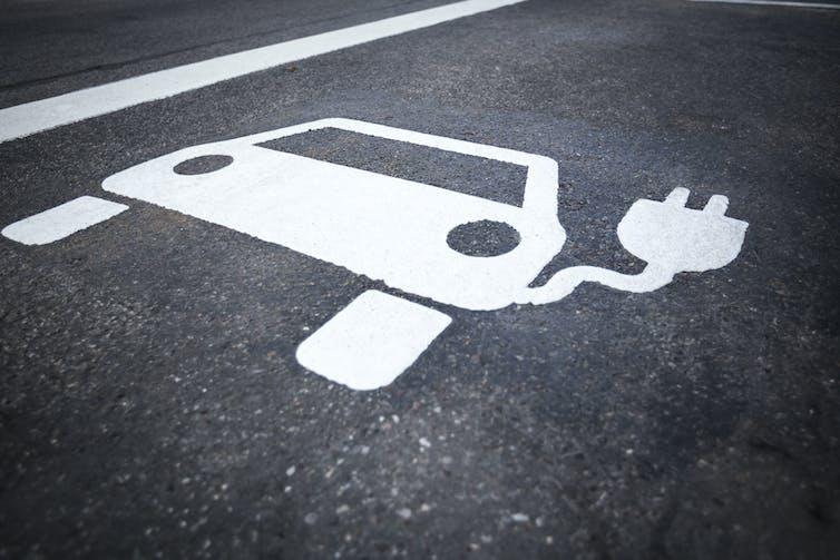 A painted electric vehicle symbol on asphalt