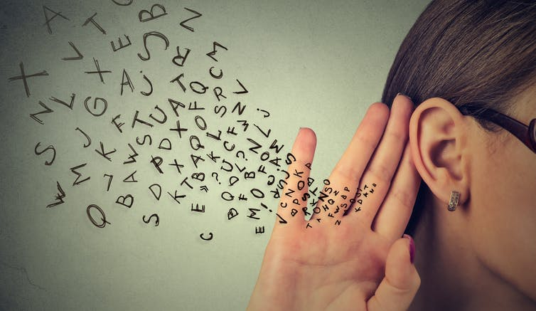 A flurry of letters goes towards the woman's ear.