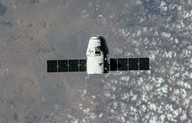 A small white cylindrical capsule floating with the Earth in the background.