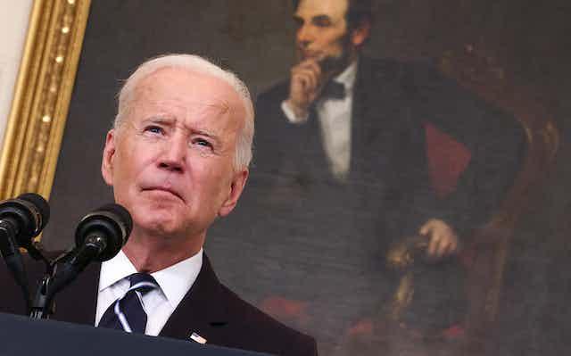 President Joe Biden addresses America in front of a portrait of Abraham Lincoln.