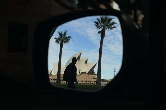A man in front of the Sydney Opera House seen in a car side-view mirror