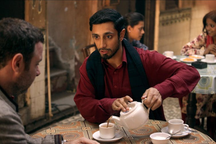 Two men sit at table drinking tea.