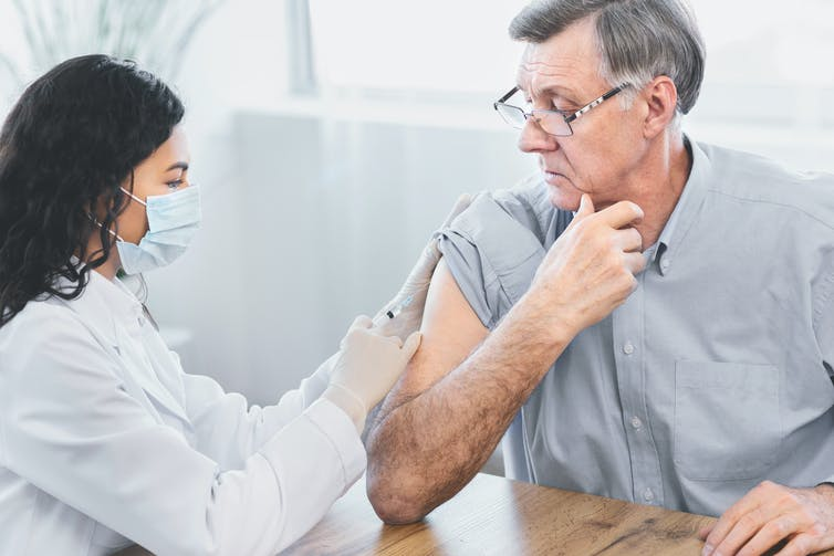 Female doctor gives elderly patient an injection into his arm.