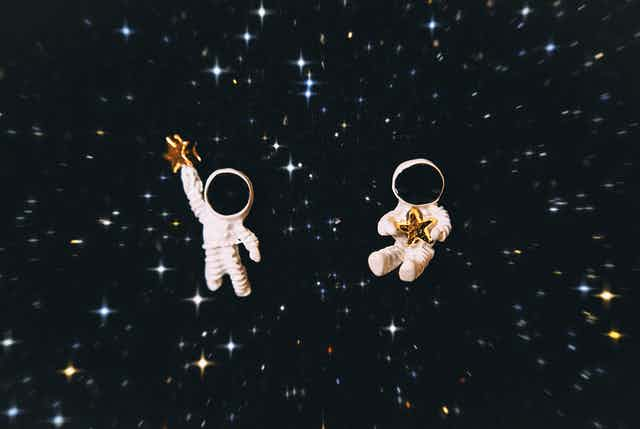 two astronaut figurines with a star background