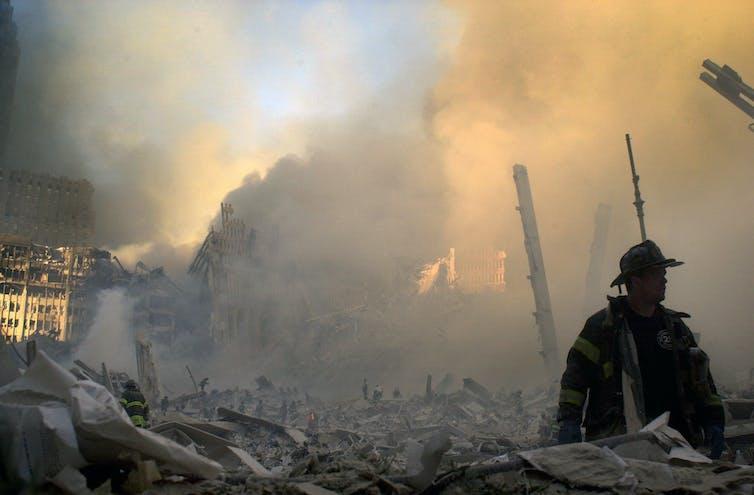 Un pompier erre dans les débris d'un édifice encore fumant