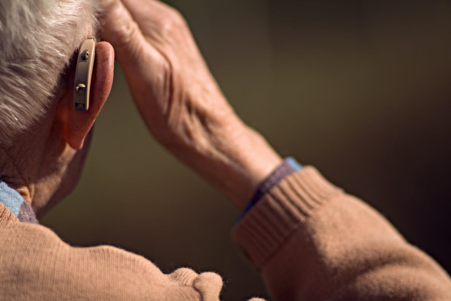 Older adult wearing hearing aid.
