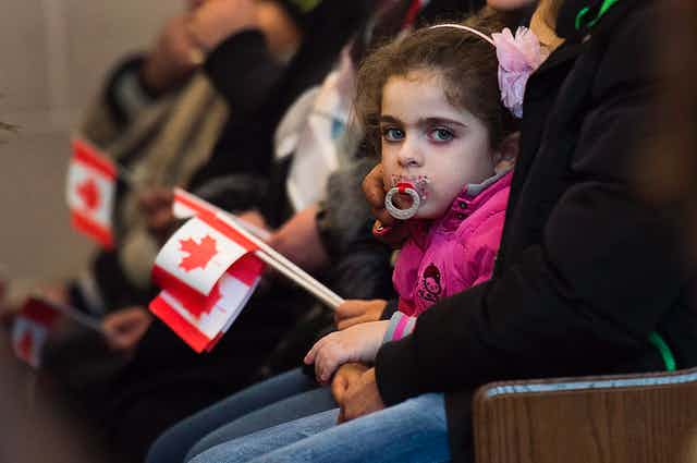 A young girl with a pacifier looks at the camera as others around her hold small Canadian flags.