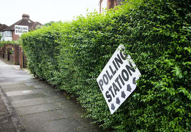 A sign for a polling station dangling precariously from a hedge.