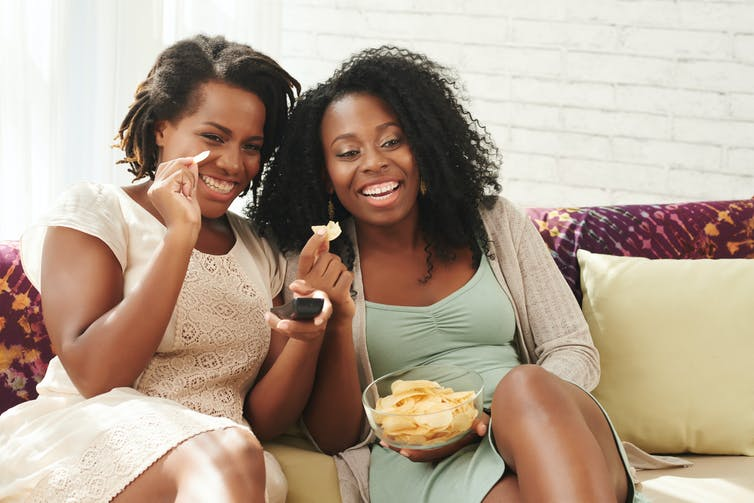 Two women eating chips from a bowl