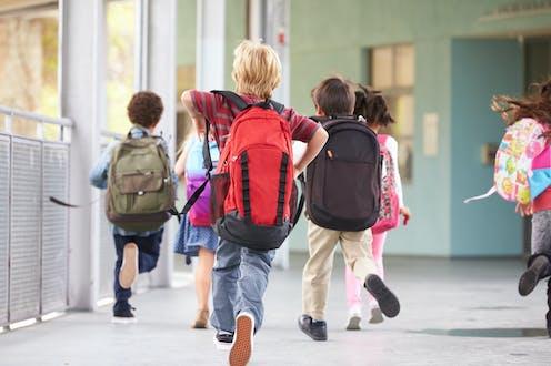 Niños corriendo por el pasillo de un centro escolar con mochilas a las espaldas.