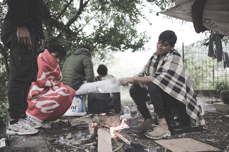 Des hommes enveloppés dans des couvertures sont assis autour d'une marmite bouillante sur un feu dans un camp à la frontière bosniaque.