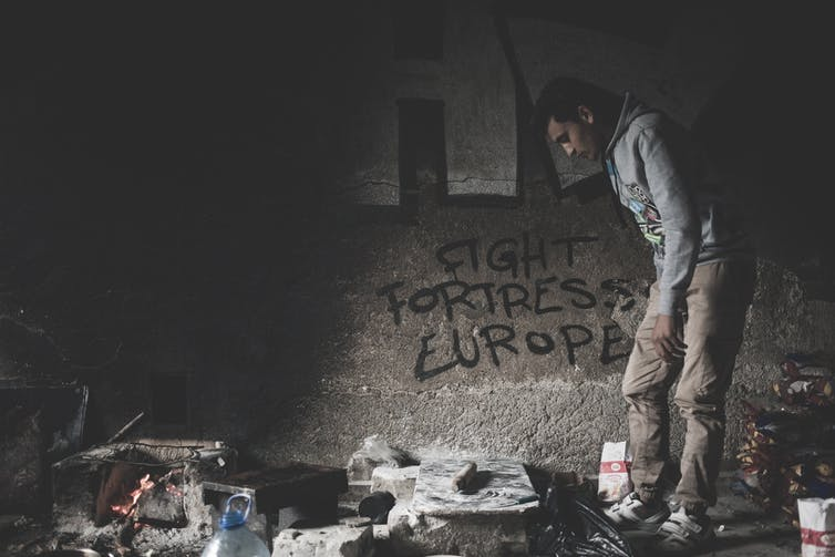 Un homme regarde autour d'une pièce sombre dans un camp de migrants. Graffiti sur le mur lit 'Fight Fortress Europe'.