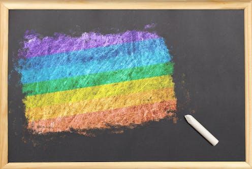 Pizarra con una bandera arcoíris pintada con tiza.