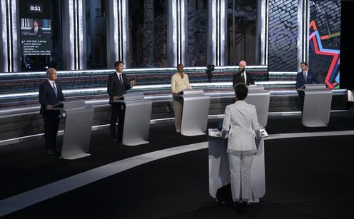 The federal party leaders standing at podiums during the French-language debate on Sept. 8, with moderator in foreground