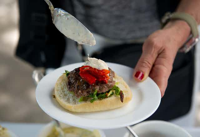 A person puts dressing on an insect burger  during a global Pestaurant event in Washington in 2014.