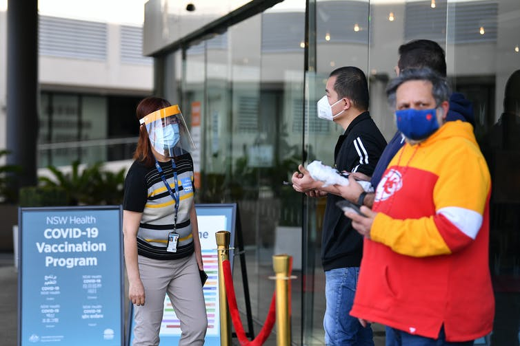 People in masks stand waiting outside a vaccination hub.
