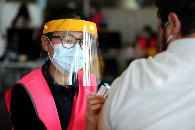 Vaccinator in a pink vest injects a vaccine into a man's arm.