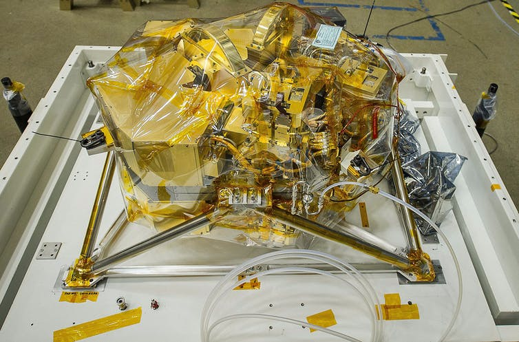 A complicated, gold-plated, hexagonal instrument standing on four silvery legs.