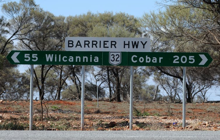 Outback road sign showing Wilcannia 55km away.